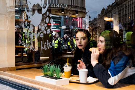 Two girls having a drink in a bar during a demonstration