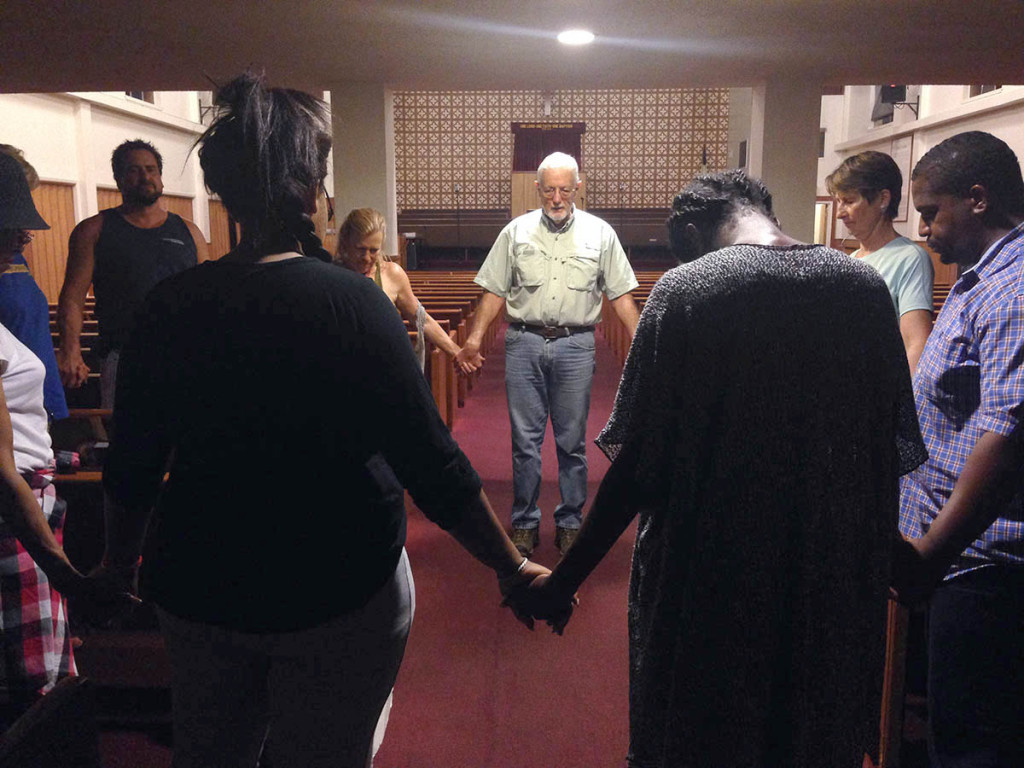 "Volunteers and clergy pray at the Bethlehem Missionary Baptist Church in Richmond following a ""night walk"" through Pullman Point. (Photo by Shawn Baldwin)"