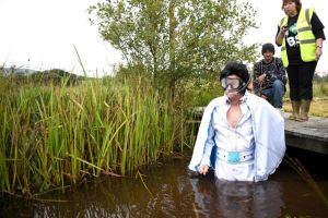 an elvis impersonator prepares to go snorkeling in a bog