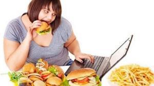 a lady binge eating while she binge watches