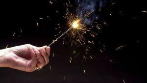 a hand holding a sparkler