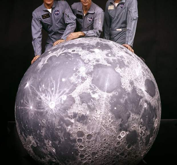 the apollo 11 crew with a model of the moon