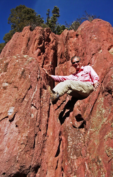 Rick Crandall climbing up a rock