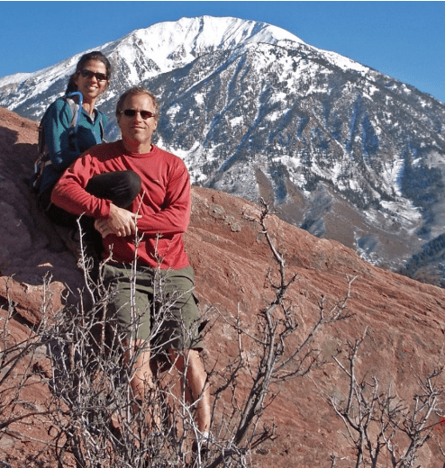Rick P and Dianna resting with a larger mountain in the distance behind them