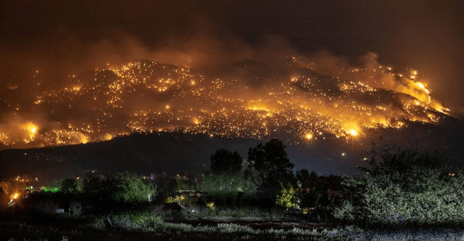 Photograph of extensive wildfires on a mountain at night.