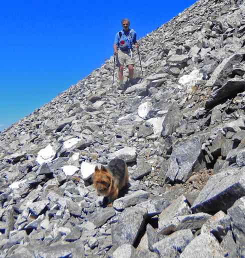 Photograph of Rick Crandall following his dog Emme down a steep, rocky path