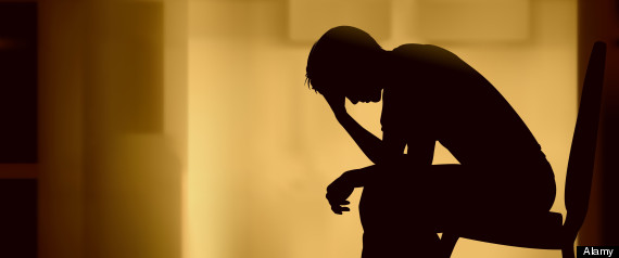 Illustrated silhouette of a man sitting with his head in his hand