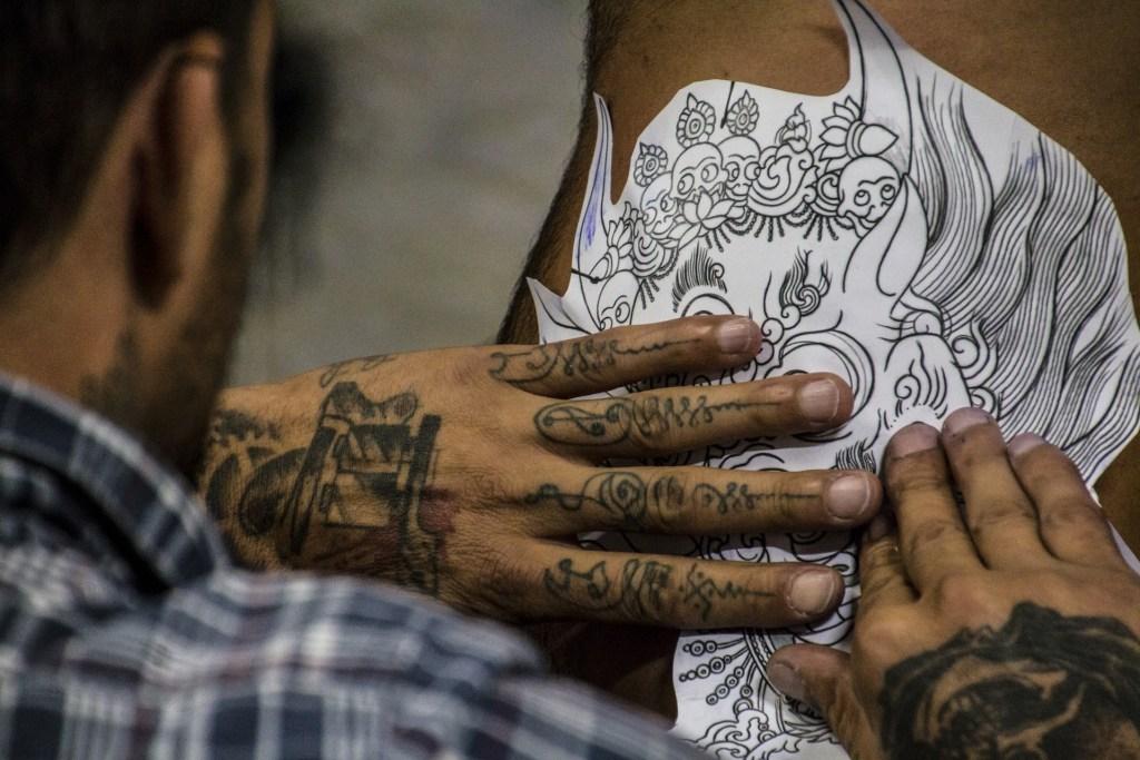 Tatoueur avec les mains et les doigts tatoués.