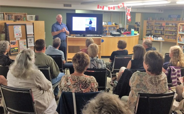 Author speaking in front of a crowd at the Main Branch in Elgin.