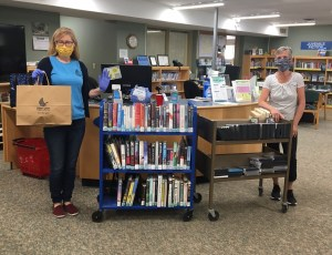 Smiling staff members have masks on and demonstrate the 2 meter or 6 foot physical distance by keeping 2 book carts between them.