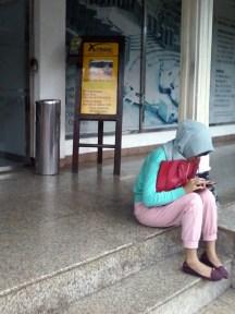 Seorang penumpang menunggu keberangkatan di pick-up point XTrans Semanggi. Hotel Kartika Chandra, Jalan Gatot Subroto Kav. 18, Setiabudi, Jakarta Selatan