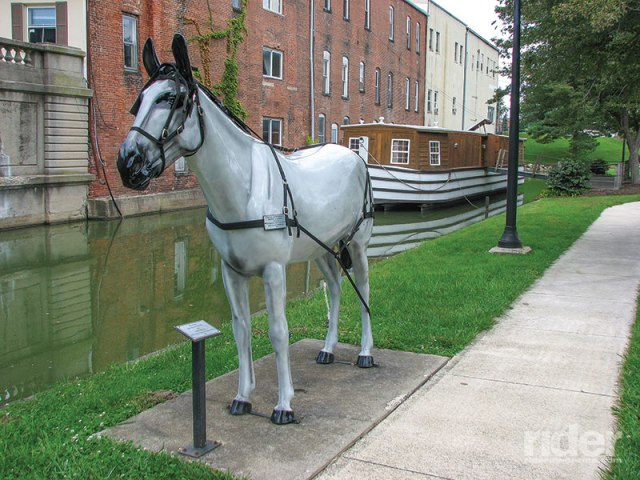 Replica of the Belle of St. Mary's canal boat tied to a model horse alongside the canal at St. Mary's, Ohio.