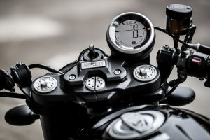 Wide clip-ons replace the standard Scramblers' tall handlebar, and a nicely machined cover sits over the ignition.