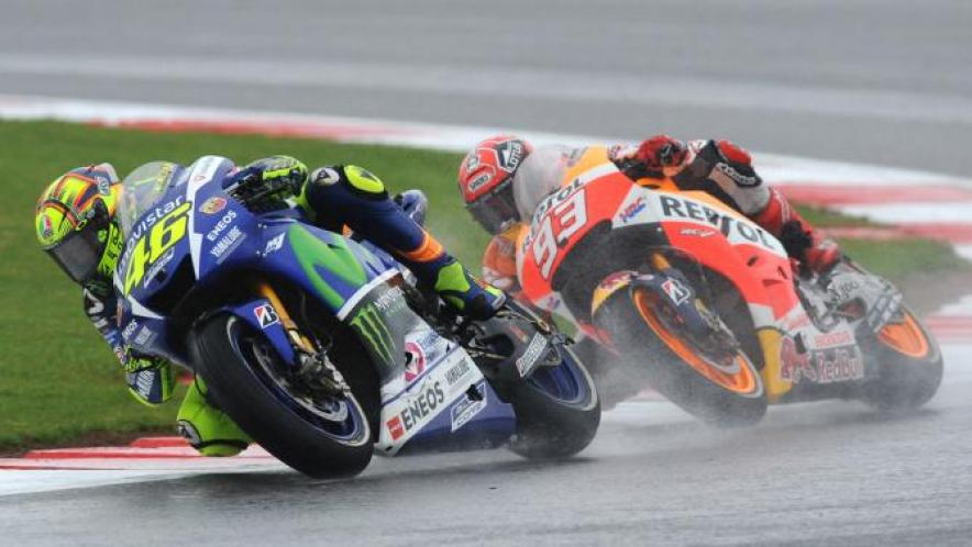 Italy's Valentino Rossi of Movistar Yamaha, left, takes a corner followed by Spain's Marc Marquez of Repsol Honda during the Moto GP race at the British Grand Prix at Silverstone, England, Sunday, Aug. 30, 2015. Rossi won the race. (AP Photo/Rui Vieira)