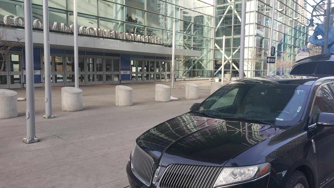 black sedan ar Denver Convention Center waiting for a customer