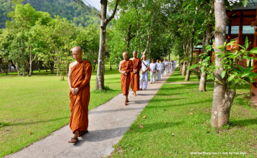 The monk leading the walking meditation, follows by the men and women