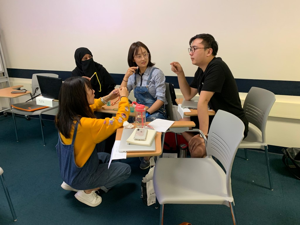 """Students engaged in a small group work activity in """"IDE 631 Instructional Design 1"""" in August 2019"""