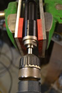 The drill is run at low rpm for a a couple of seconds.  The drill is removed and the bolt cutting tool retracted.