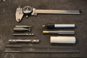 In addition to a milling machine, we will use the following tools to install sights.  Dovetail files (bottom), solid carbide endmills (lower center left), carbide dovetail cutters (upper center left), calibers (top), edge finder (upper center right) and a brass and plastic drift (lower center right).