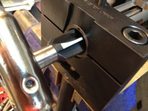 We run the receiver reamer into the action to clean the minor diameter of the thread and square the receiver lugs.