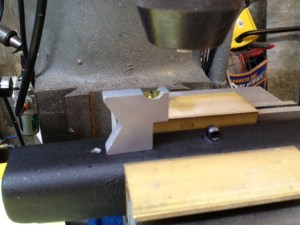 With the action removed, and the epoxy set, the bottom of the stock is leveled in the vise.