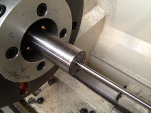 The barrel is run through the lathe's headstock and secured with spiders on both ends.  A PTG grizzly rod, with the appropriately sized bushing is placed into the bore.