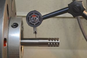Since the bore may not be in concentric to the outside of the barrel, I use an indicator to dial in the outside of the barrel.  This ensures the brake will blend with the barrel after its turned.