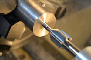 Using a piloted 60-degree center drill, I cut a counter bore to mate against the centers on the lathe.
