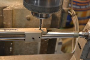 """The action is rotated on the rotary table until the bolt stop slot will clear the stock.  A 3/16"""" cut is made into the action."""