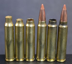 Forming the 6.5 Patriot Combat Cartridge (PCC) from virgin brass. From left to right: virgin 223 Remington case, case trimmed to length, case necked up to 6.5mm, loaded 6.5 PCC (pre fire form), fire formed 6.5 PCC case, and loaded, fire formed 6.5 PCC case.