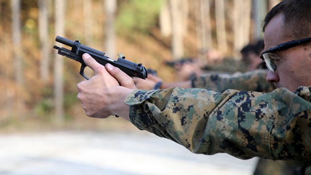 Marines paticipating in the EOTG Urban Sniper Course fire at designated targets as the students fire at targets aboard Marine Corps Base Camp Lejeune, N.C., December 4, 2014. Pistol qualifications areessential for room clearing and close-quarter shooting. After students fire the pistol they search and assess the area making sure the perimeter is safe. (U.S. Marine Corps photo by Pfc. Immanuel M. Johnson)