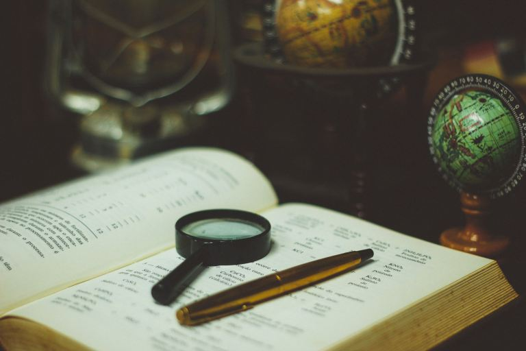 Open book with writing on it and a pen and magnifying glass resting on the open book.