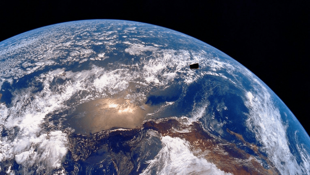 This is an image of planet Earth from space. The planet is mostly blue, with brown surfaces indicating continents and white clouds over the atmosphere.