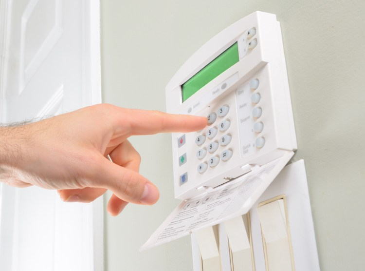 Person pressing code on house alarm