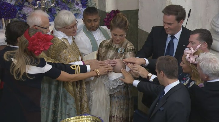 Godparents lay hands on Prince Nicolas for a blessing.