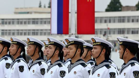 Chinese sailors stand in formation in front of national flags of Russia