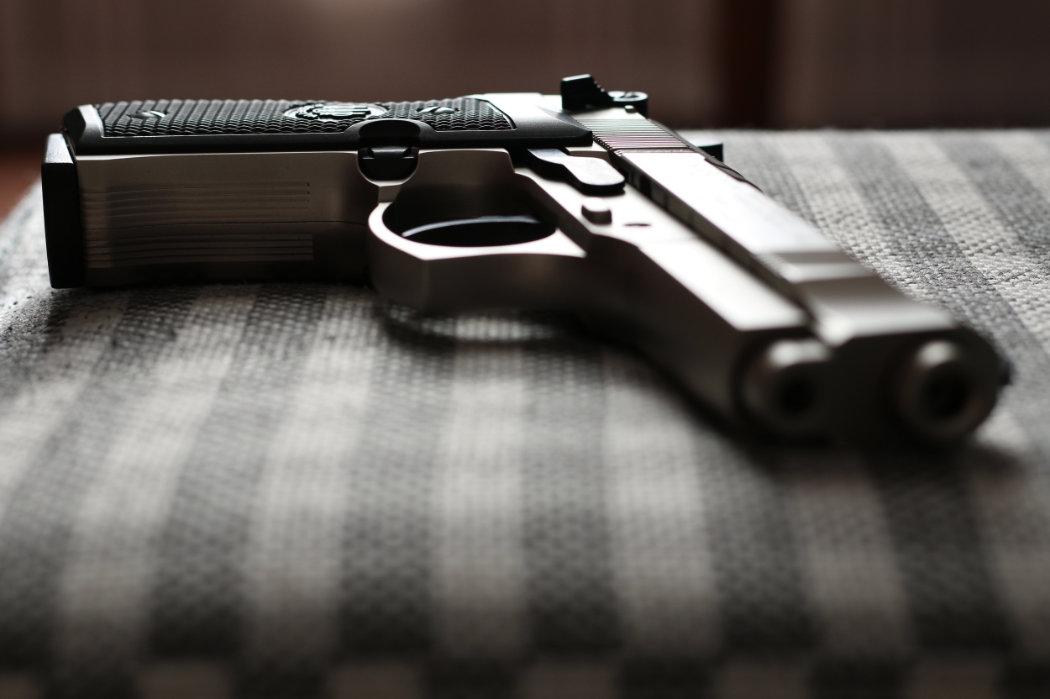 handgun on checkered chair