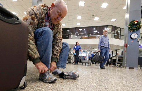 A passenger puts his shoes on after going through security at the Salt Lake City international airport