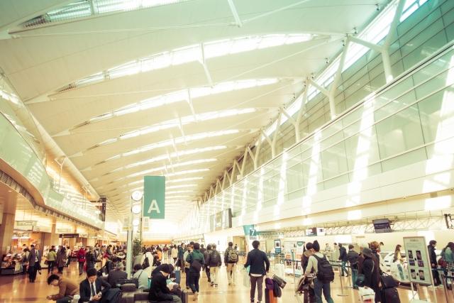 手荷物を持ったお客さんでいっぱいの羽田空港