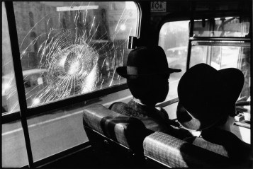 On a public bus in Jerusalem, two Orthodox Jewish Israelis ignore a window damaged by stone throwing Palestinians.
