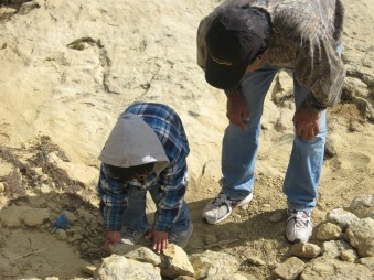 Peter Pino and his granddaughter Vivian building a one-rock dam.