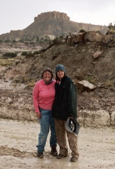 Ann Beckett and Sarah Sisk standing in the mud after a long day of work.