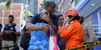Brazil, Family members and friends wait for word from firefighters about victims trapped in the rubble in the Muzema favela community.