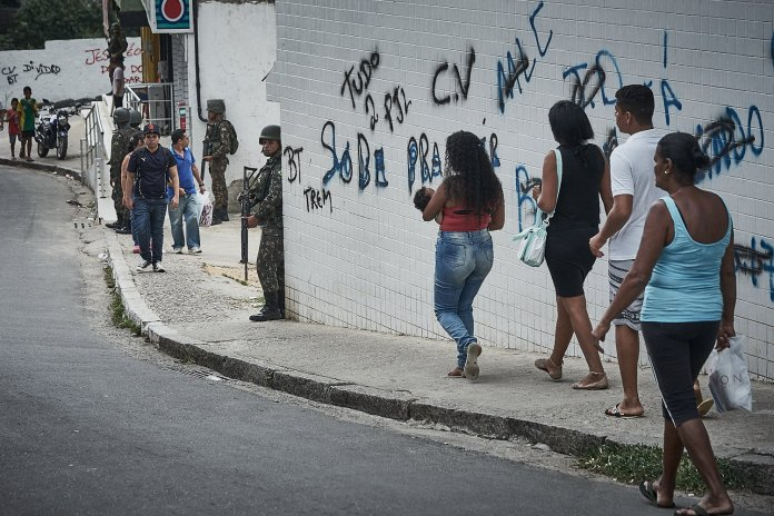 """Residents of Praca Seca walk the street during a military operation targeting organized crime in the area. The graffiti on the wall reflects the frequent changes in """"ownership"""" between militias and the narco-gang Comando Vermelho.(Photo: C.H. Gardiner)"""
