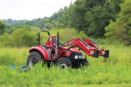 Glenn mowing at his farm with the river and prairie behind.