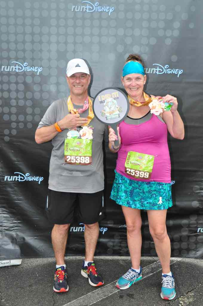 Disney Wine and Dine Half Marathon Weekend - Your Questions Answered|Run Disney Ripped Jeans and Bifocals Smiling couple in running clothes in front of run Disney sign