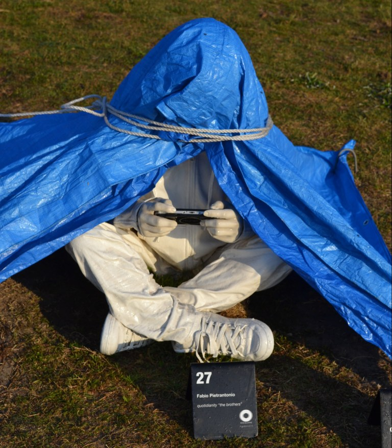 Sculpture of a seated person with head under a plastic tarpaulin using a smartphone