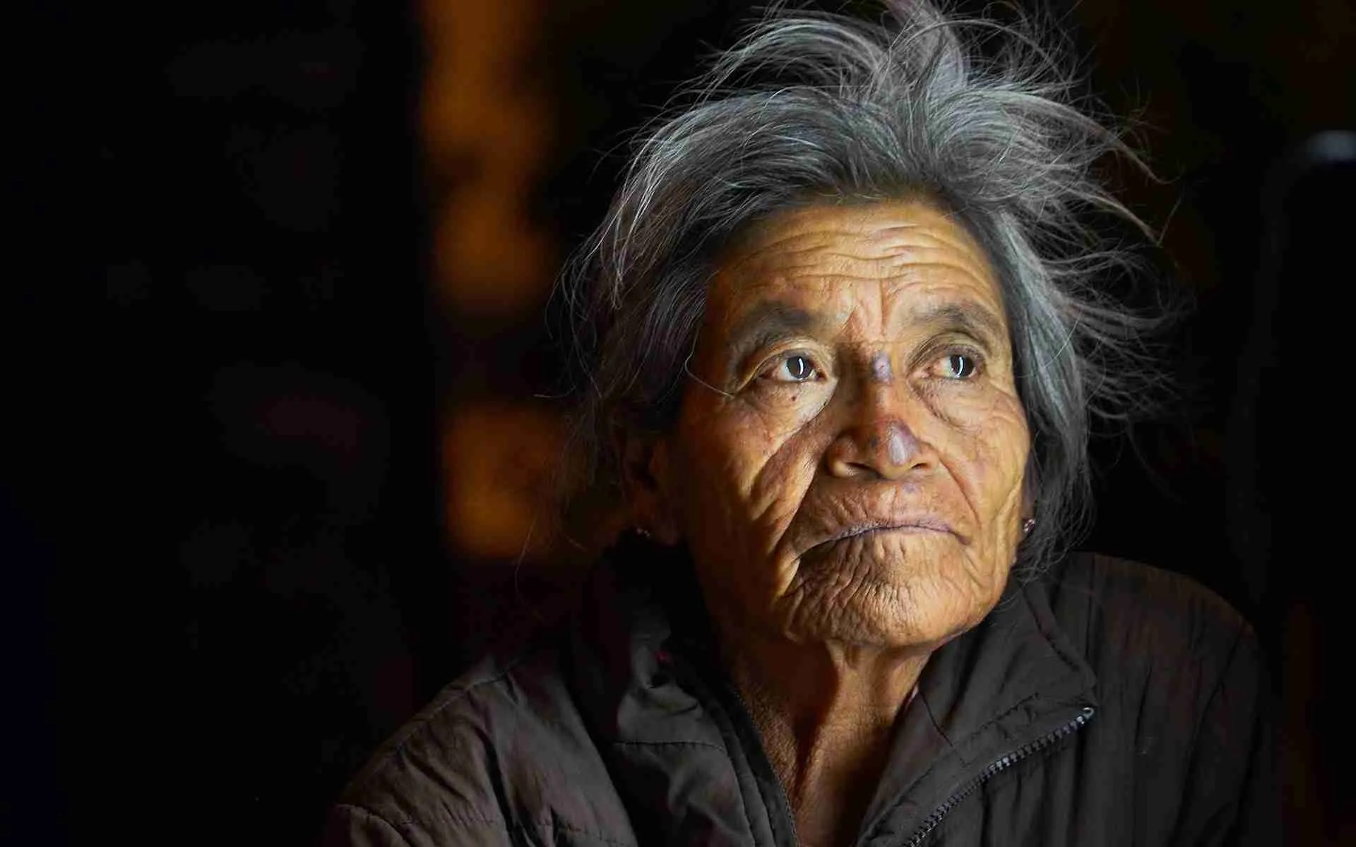 A portrait of an older woman looking pensive.