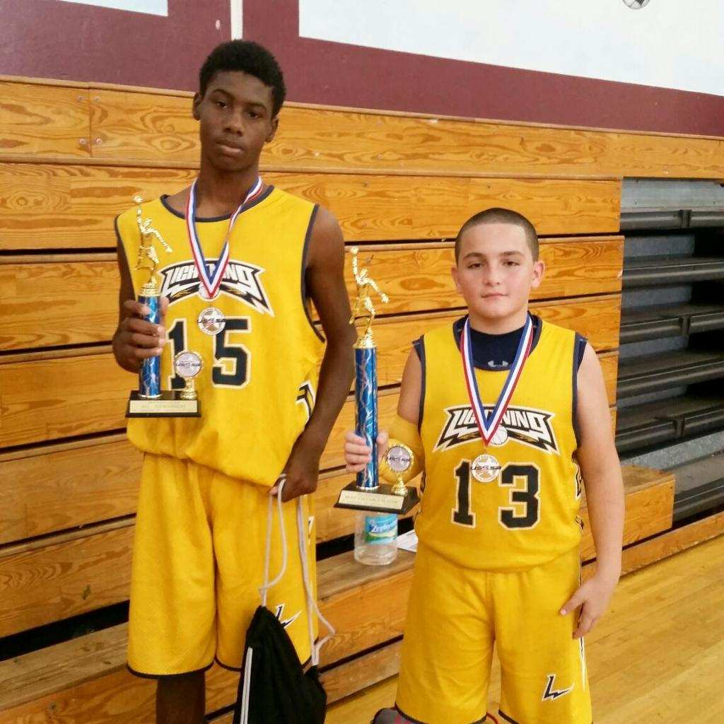 Craig Starks (#15) and  Julian Garcia (#13) hold up trophies after a successful tournament.