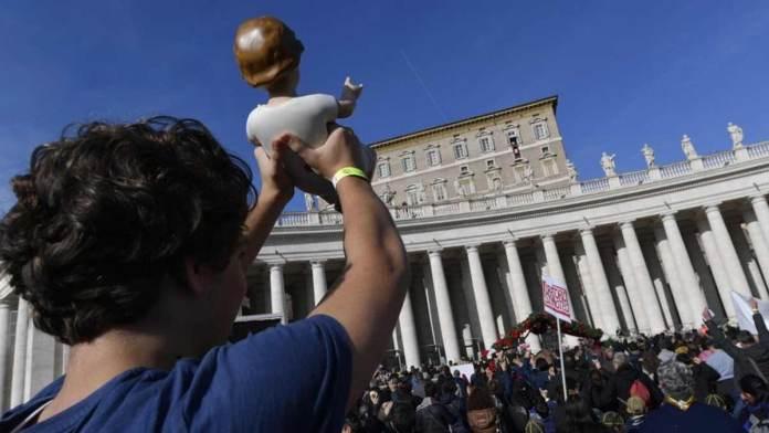 Un ragazzo porta un bambinello del presepe in piazza San Pietro per la benedizione